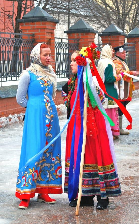 Aktorzy ubierali w kolorowych krajowych kostiumach witają ludzi na ulicie obraz stock