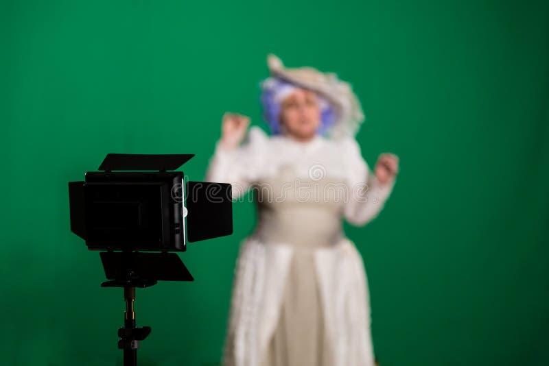Aktrisskottet på grön bakgrund Belysningsutrustning i studion arkivfoto