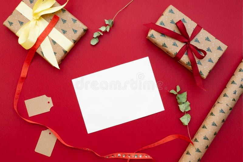 aktuell weihnachtspakete för jul Gåvor som packas i hantverkpapper, bokstav för hälsningkort, pilbåge, torkade blommor på röd bak royaltyfri fotografi