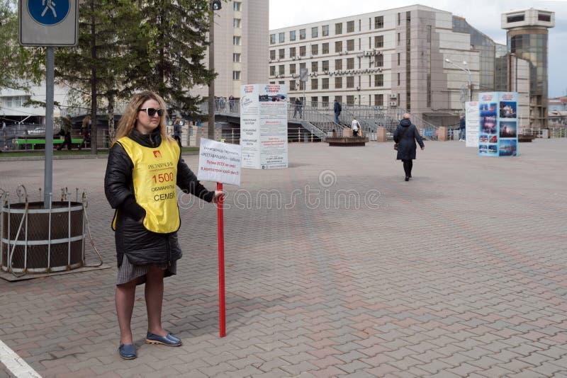 Aktywista z inskrypcją na ubraniach: 1500 oszukiwali rodziny - stojaki przeciw tłu miasto obrazy stock