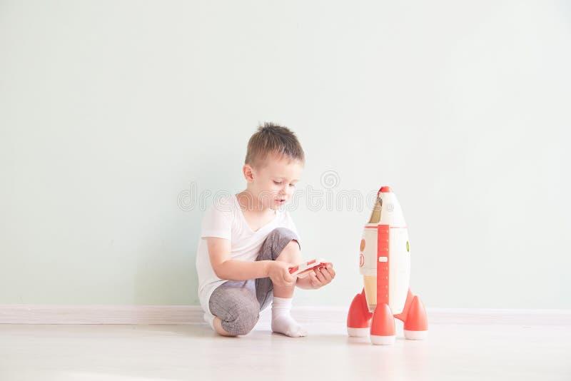 Aktywna chłopiec bawić się rakiet zabawek, dziecko seansu rakiety zabawkę z, dzieci lub berbecia uczenie i obrazy stock