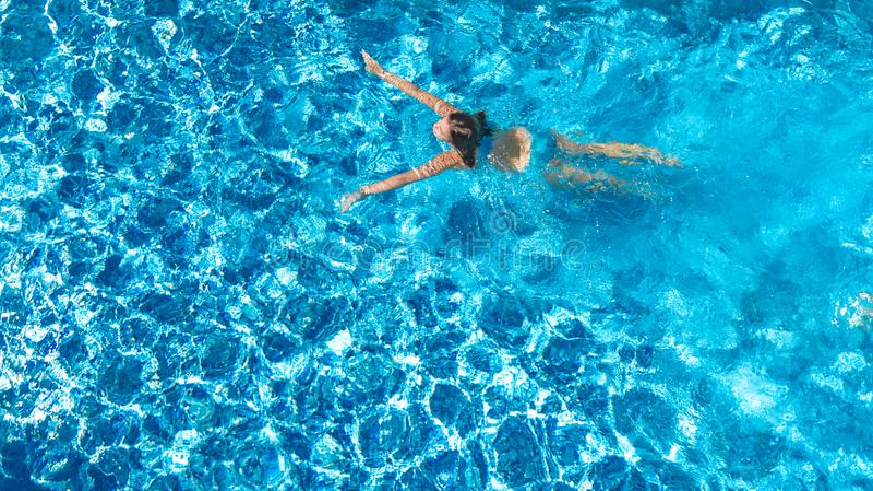 Aktywna dziewczyna w basenu trutnia powietrznym widoku z góry, młoda kobieta pływa w błękitne wody, tropikalny wakacje obraz royalty free