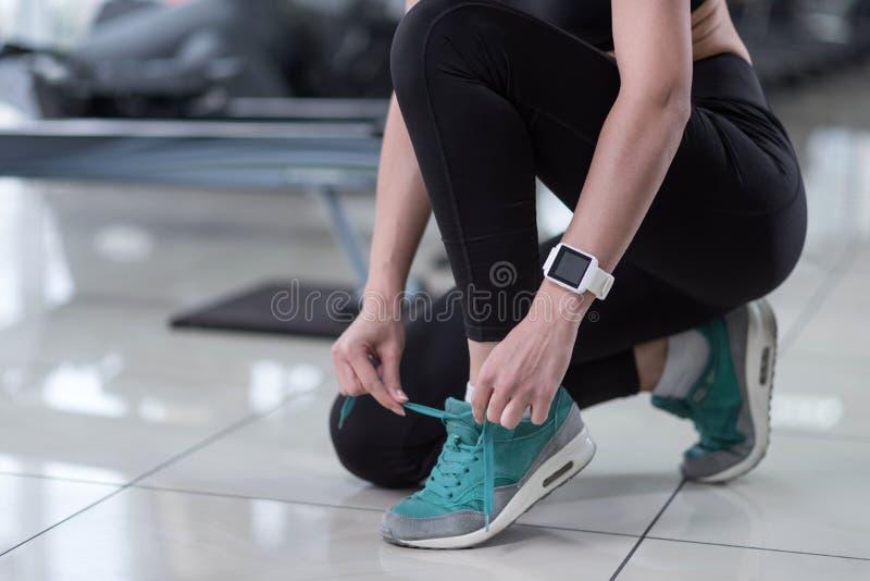 Aktywna dziewczyna wiąże jej shoelaces w gym fotografia royalty free