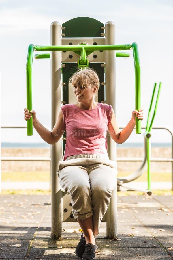Aktywna kobieta ćwiczy na klatki piersiowej prasie plenerowej obraz stock