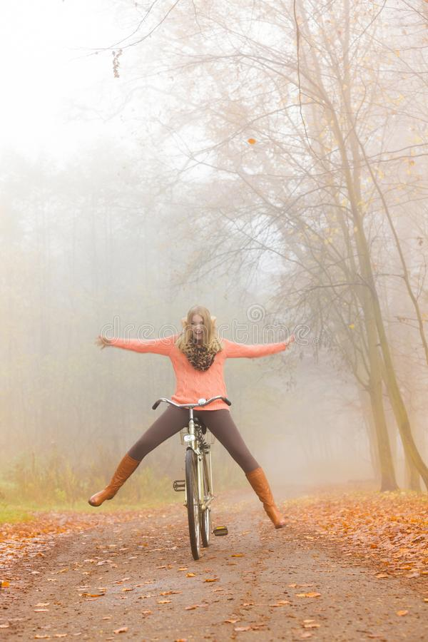 Aktywna kobieta ma zabawy jazdy rower w jesień parku fotografia stock