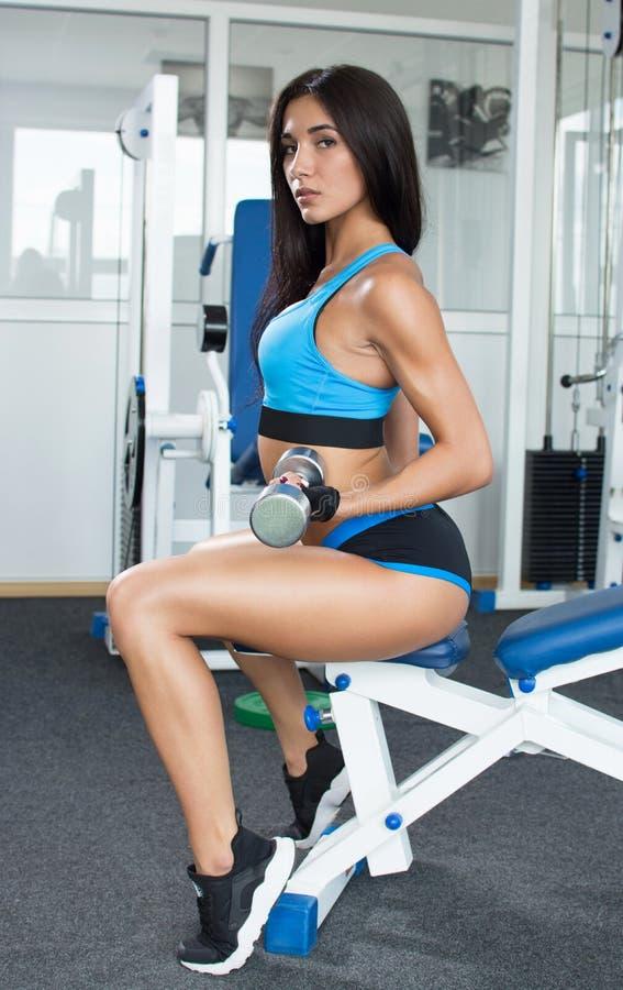Aktywna kobieta w sportswear obsiadaniu z ukosa i angażującym z dumbbells w gym Bawi się odżywianie Błyszcząca skóra obrazy royalty free