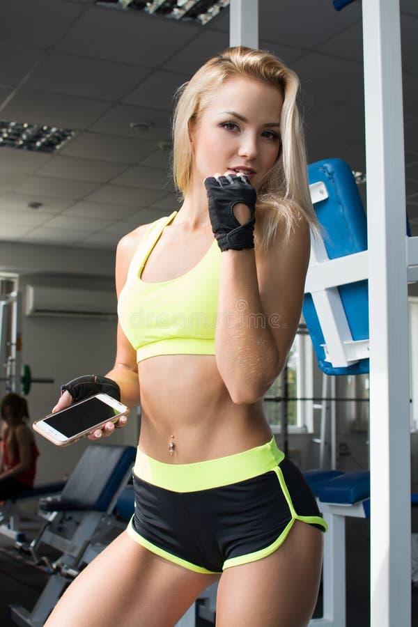 Aktywna kobieta w sportswear używać mądrze telefon w gym Zostać lepiej Siła wola piękne ciało obrazy royalty free