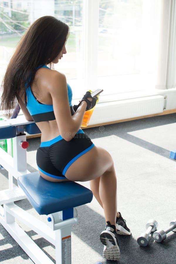 Aktywna kobieta w sportswear używać mądrze telefon w gym Zostać lepiej Siła wola piękne ciało zdjęcia royalty free