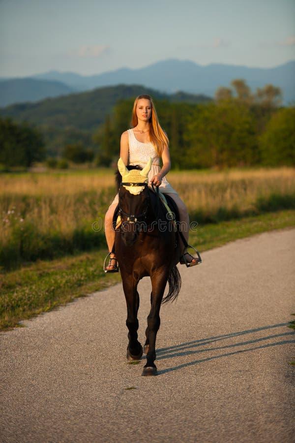 Aktywna młodej kobiety przejażdżka koń w naturze fotografia royalty free