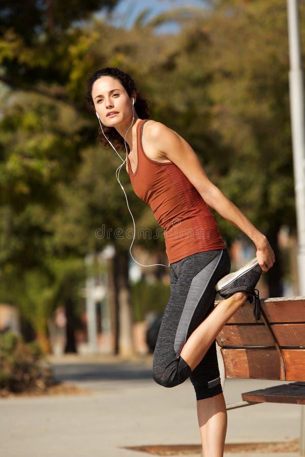 Aktywna młodej kobiety rozciągania noga outside fotografia stock