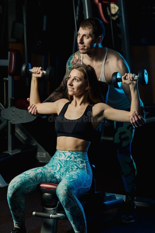 Aktywna piękna sprawność fizyczna modela dziewczyna i jej trenera szkolenie z dumbbells na ławce w gym obrazy royalty free