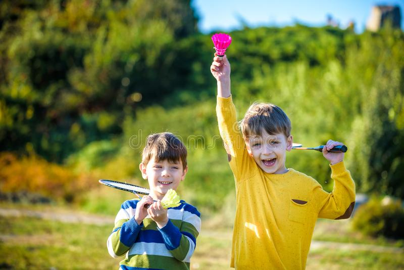 Aktywna preschool dziewczyna, chłopiec bawić się badminton w plenerowym sądzie w lecie i Dzieciak sztuki tenis Szkoła bawi się dl zdjęcia royalty free