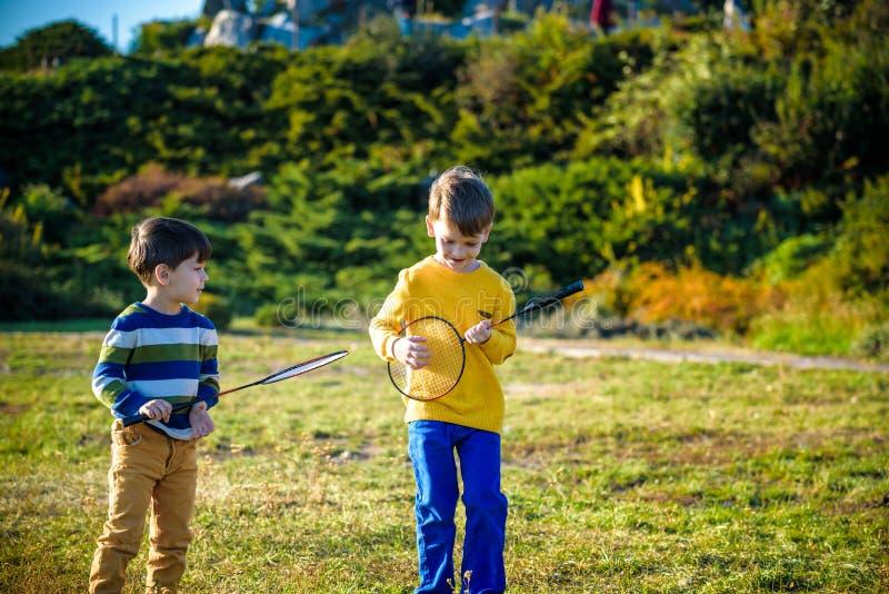 Aktywna preschool dziewczyna, chłopiec bawić się badminton w plenerowym sądzie w lecie i Dzieciak sztuki tenis Szkoła bawi się dl obrazy royalty free