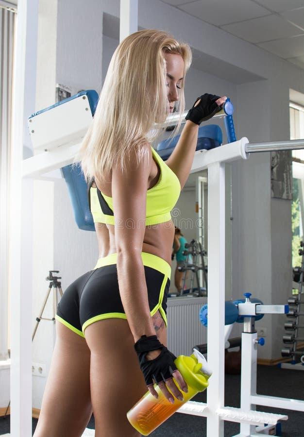 Aktywna seksowna kobieta w sport zieleni ubrań stojakach przy sporta gym wyposażeniem Bawi się odżywianie Amino kwasy zdjęcia royalty free