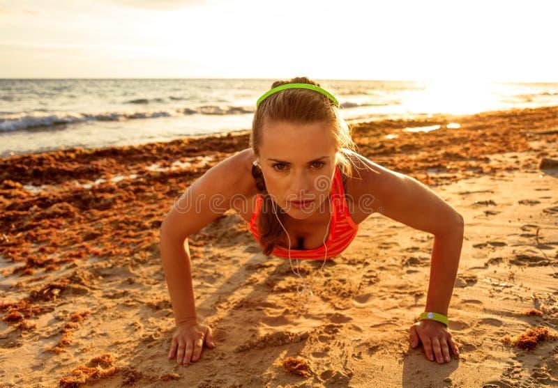 Aktywna sprawności fizycznej kobieta w sportswear na plaży robi pushups obraz royalty free