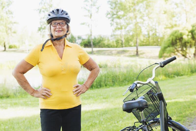 Aktywna starsza kobieta jechać na rowerze i relaksuje przy wsią w jaskrawym świetle słonecznym zdjęcie stock