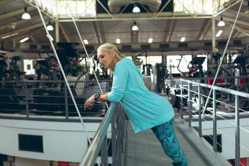 Aktywna starsza kobieta opiera na poręczu w sprawności fizycznej studiu obrazy stock