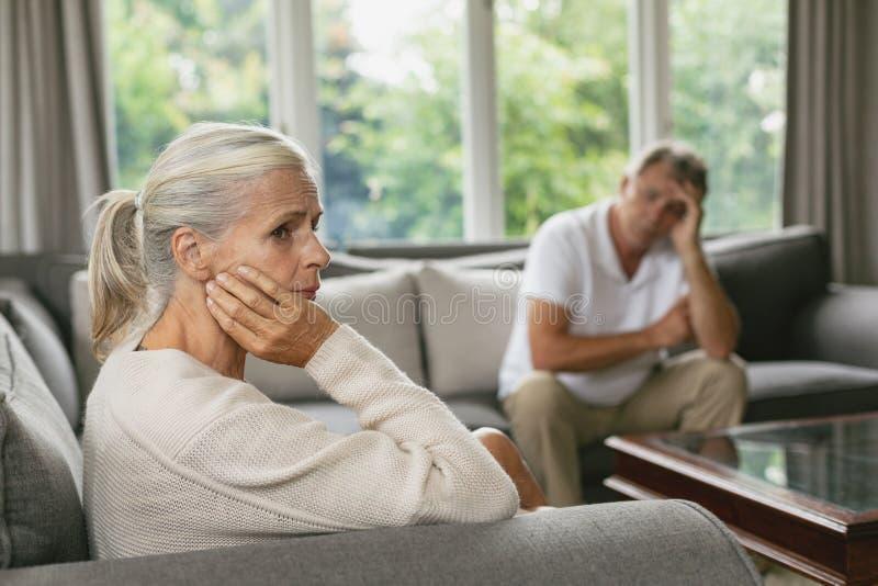 Aktywna starsza kobieta z ręką na twarzy obsiadaniu na kanapie w wygodnym domu fotografia stock