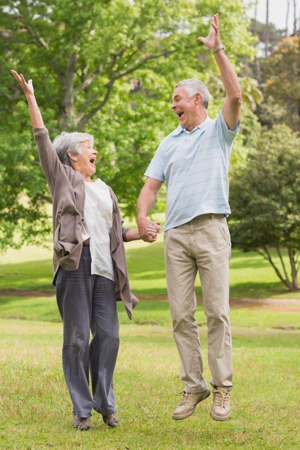 Aktywne starsze pary mienia ręki i doskakiwanie w parku zdjęcia stock
