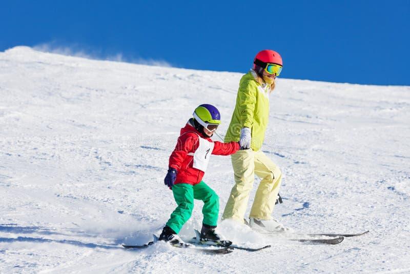 Aktywnego nauczania syna narciarstwa mienia macierzyste ręki zdjęcie royalty free