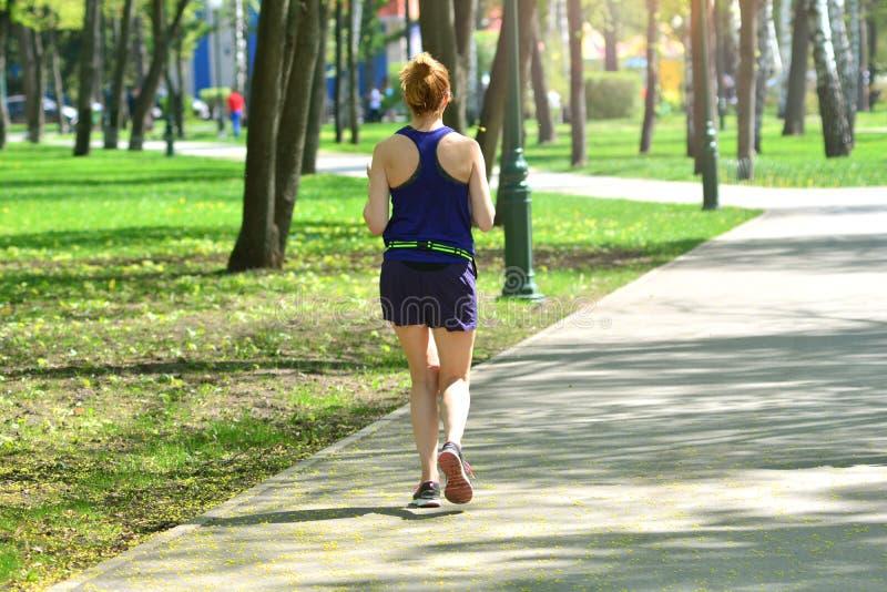 _ Aktywni kobieta bieg krzy?uj? w lato parku zdjęcia stock