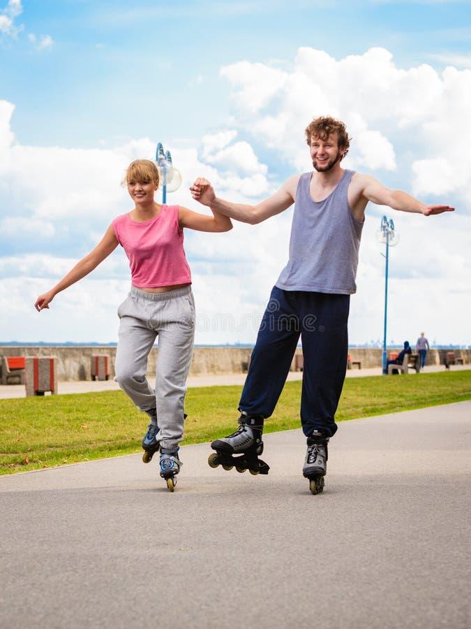 Aktywni młodzi ludzie przyjaciela rollerskating plenerowego zdjęcia stock