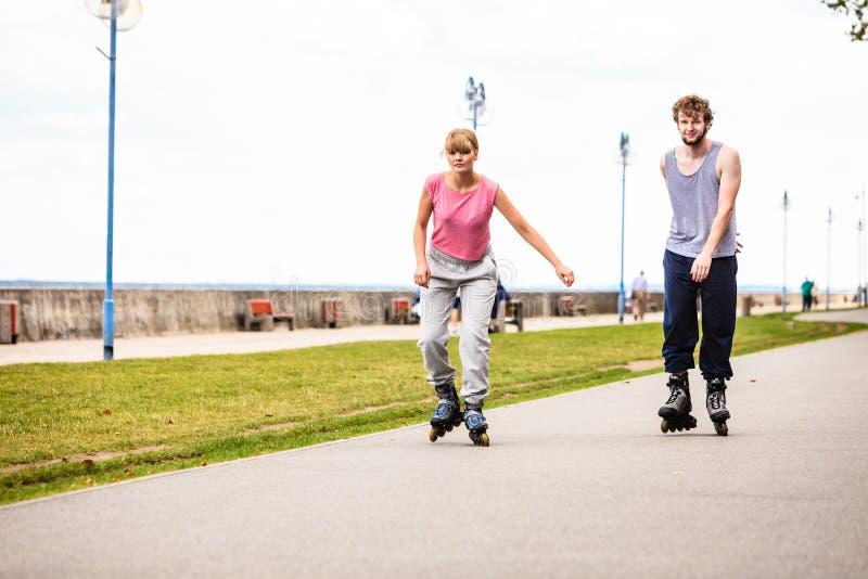 Aktywni młodzi ludzie przyjaciela rollerskating plenerowego zdjęcie stock
