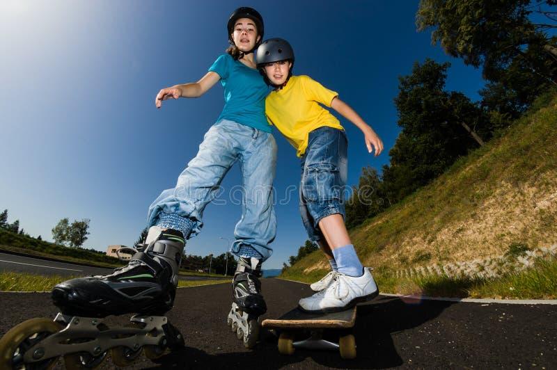 Aktywni młodzi ludzie - rollerblading, jeździć na deskorolce obraz stock