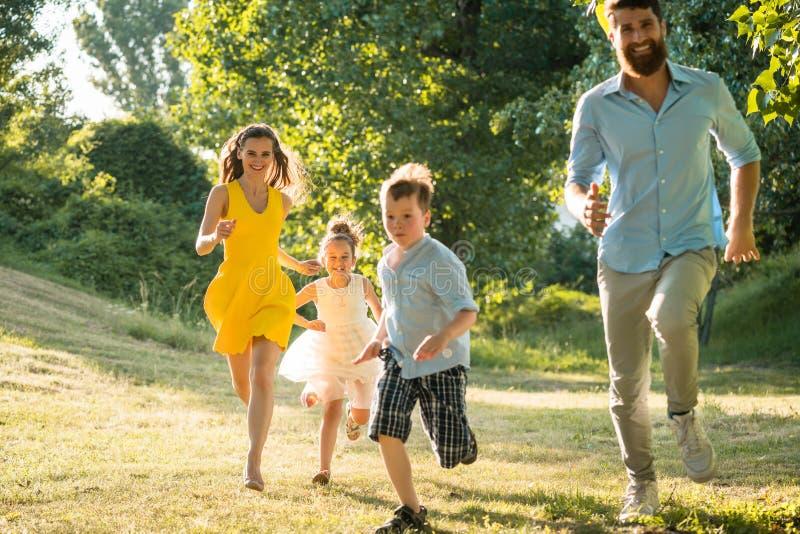 Aktywni potomstwa wychowywają z zdrowym stylem życia biega wpólnie zdjęcie royalty free