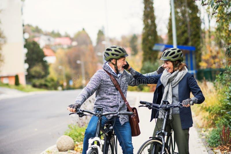 Aktywni starszy ludzie z electrobikes wita outdoors na drodze w miasteczku obraz royalty free