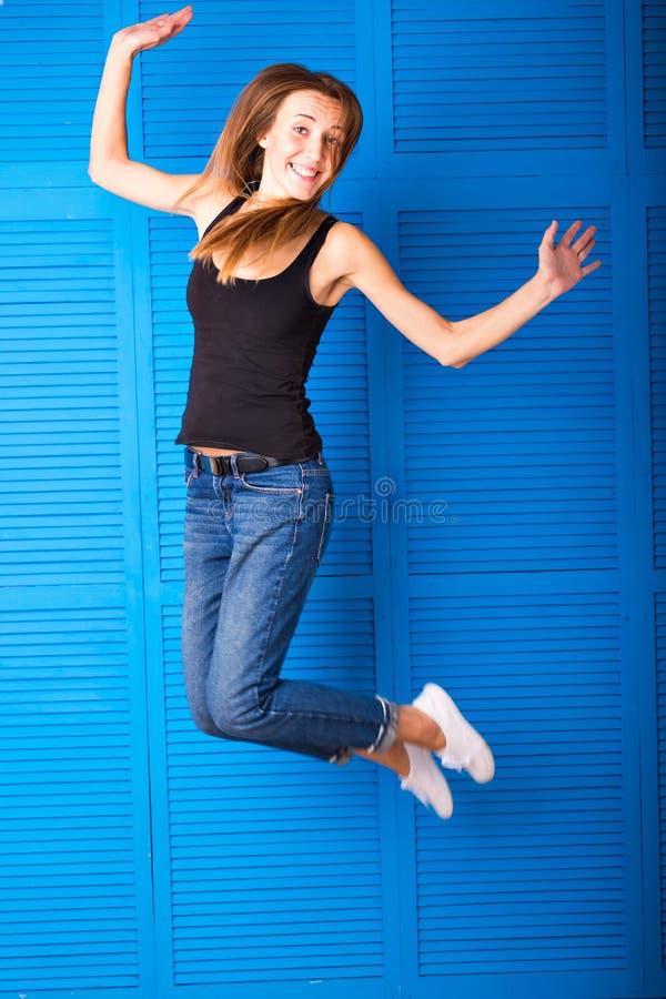 Aktywności i szczęścia pojęcie - uśmiechnięta nastoletnia dziewczyna w białym pustym koszulki doskakiwaniu zdjęcie stock