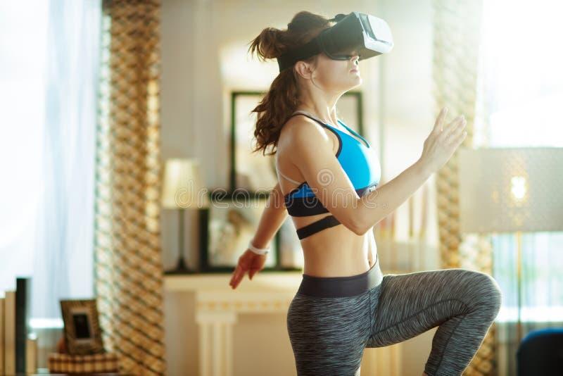Aktywny bawi się kobiety przy nowożytnym domem w VR szkieł treningu fotografia royalty free