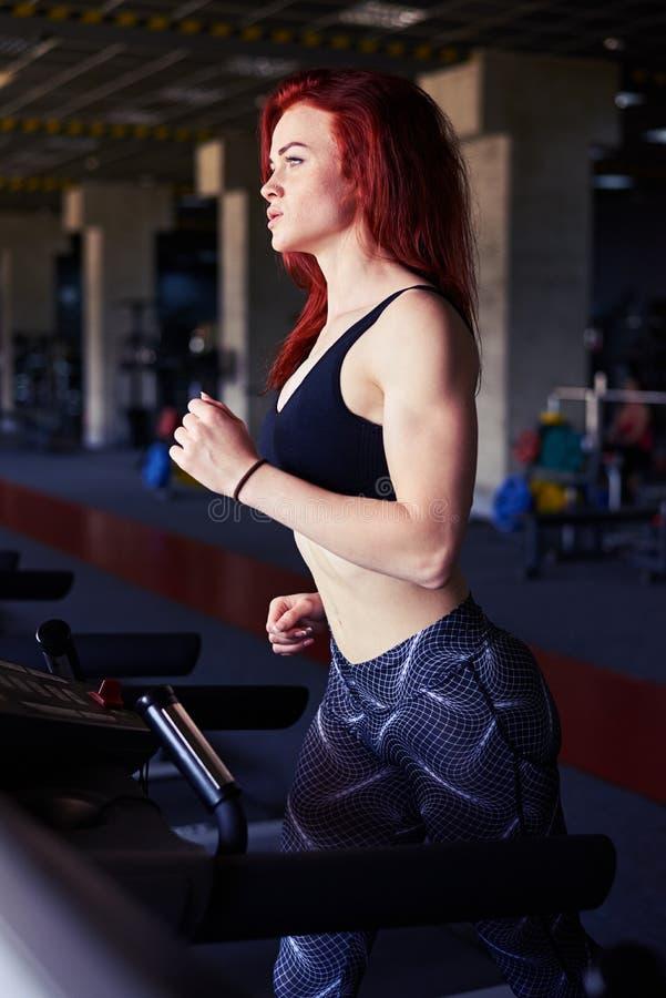Aktywny kobieta bieg na karuzeli przy gym ćwiczyć obraz royalty free