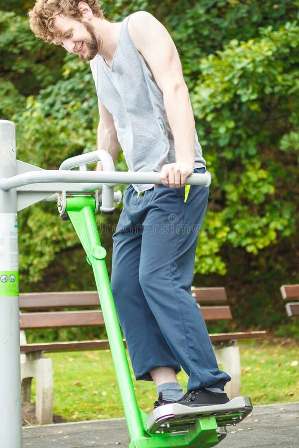 Aktywny mężczyzna ćwiczy na narciarskim trenerze plenerowym obrazy stock