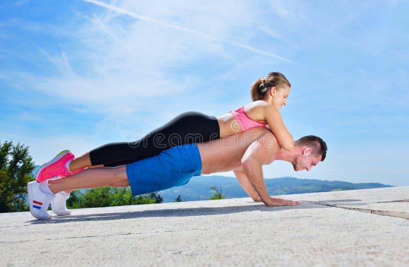 Aktywny młody człowiek i kobieta ćwiczy robić pchamy podnosimy obraz royalty free
