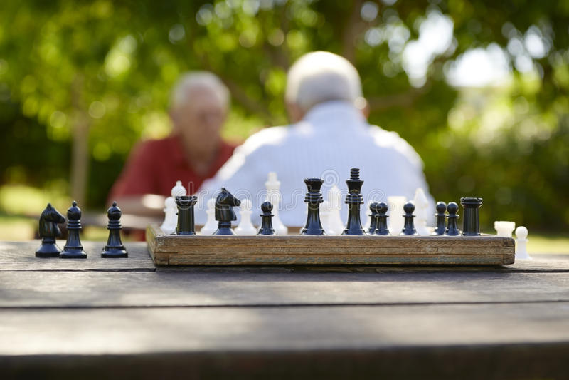 Aktywny przechodzić na emeryturę ludzi, dwa starego przyjaciela bawić się szachy przy parkiem obraz stock