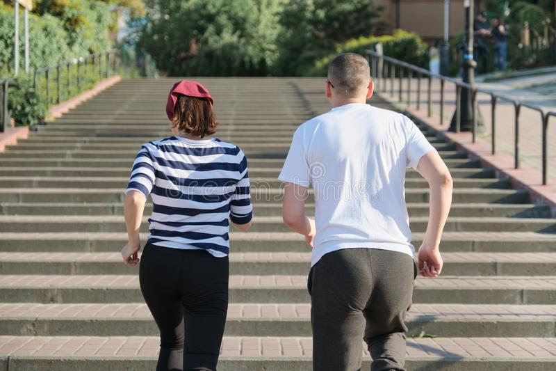 Aktywny zdrowy styl ?ycia dojrza?a para W ?rednim wieku m??czyzna i kobieta biega na pi?trze, widok od plecy zdjęcie stock