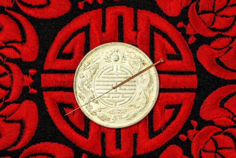 Akupunkturnadel auf chinesischer Münze und Symbol für Unsterblichkeit lizenzfreie stockfotografie
