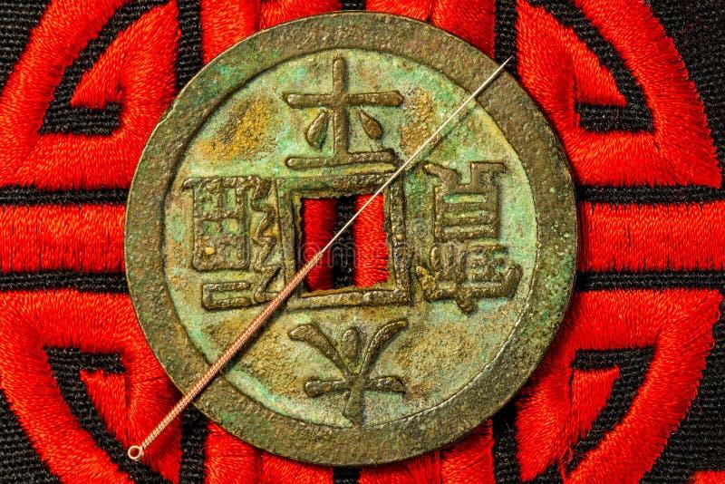 Akupunkturnadel auf chinesischer Münze und Symbol für Unsterblichkeit stockbilder