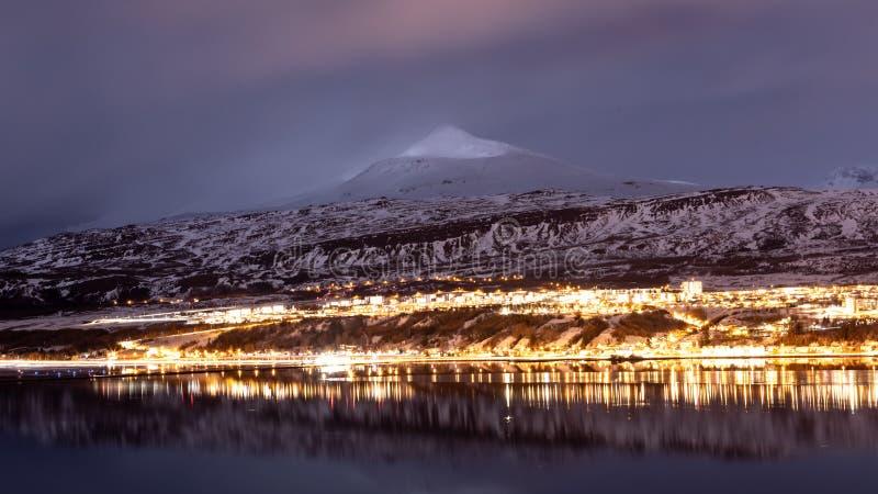 Akureyri, luzes da cidade de Islândia durante horas azuis com um contexto de montanhas do gelo imagens de stock royalty free