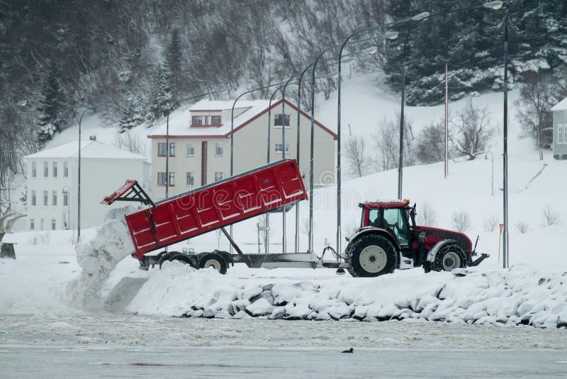 Akureyri Snow Disposal. Tipper truck dumping cleared snow into Eyjafjordur fjord in Akureyri, Iceland royalty free stock photo