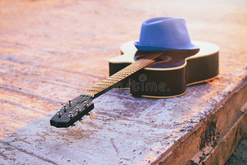 Akustikgitarre auf einem Abendstrand tonte im Sonnenlicht im Retrostil stockfotografie
