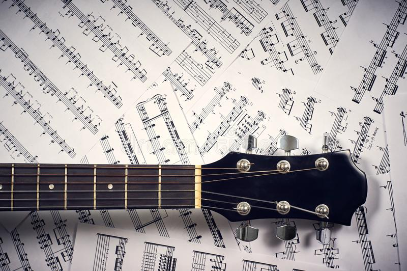 Akustikgitarre des Fingerboard auf Anmerkungen eines Hintergrundblattes stockfotos