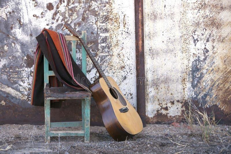 Akustikgitarre, die auf einem Stuhl sich lehnt lizenzfreies stockbild