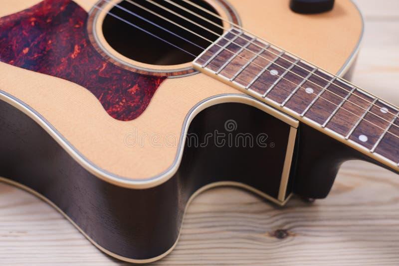 Akustikgitarre, die gegen einen hölzernen Hintergrund stillsteht stockfotografie