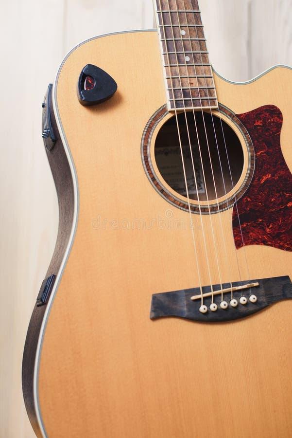 Akustikgitarre, die gegen einen hölzernen Hintergrund stillsteht stockbilder