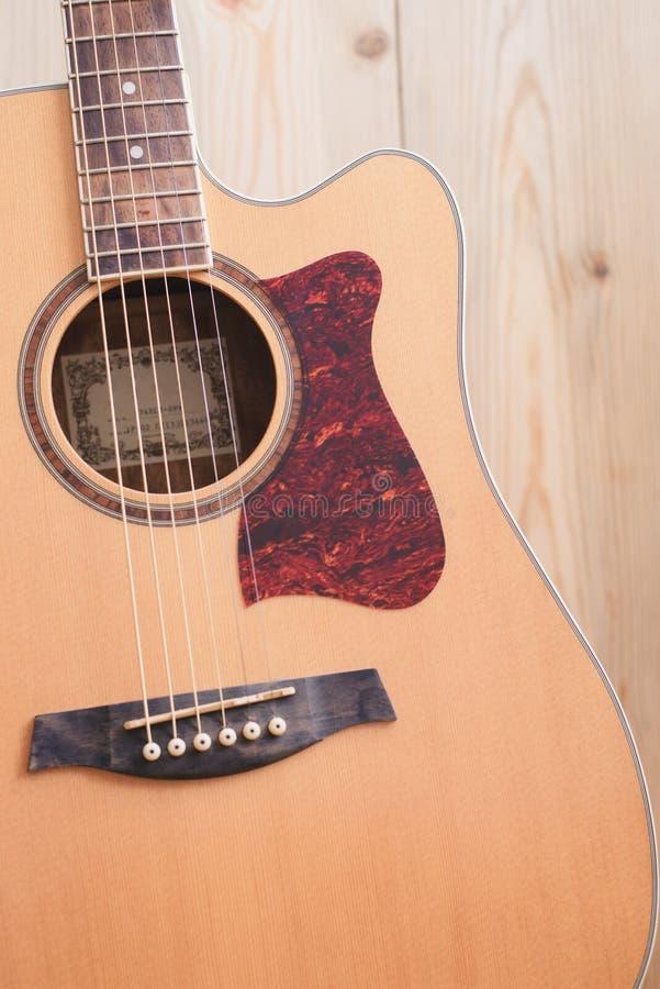 Akustikgitarre, die gegen einen hölzernen Hintergrund stillsteht stockfoto