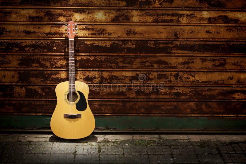 Akustikgitarre gegen rostige Gatter stockfoto