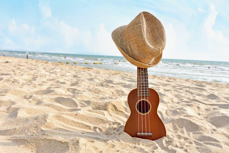Akustische Ukulelestellung im sandigen Strand mit Hut lizenzfreie stockfotografie