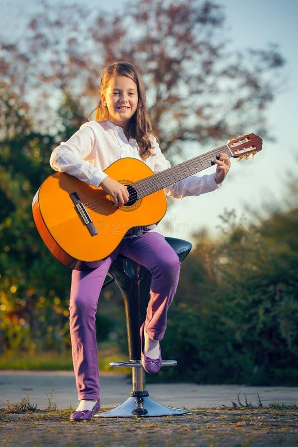 akustisk flickagitarr little som leker royaltyfri fotografi